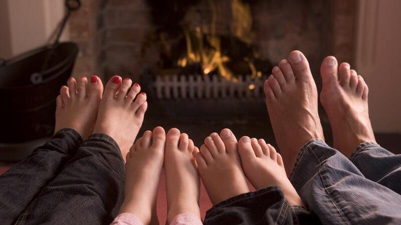 Füße einer Familie, Eltern, zwei Kinder vor Kaminfeuer