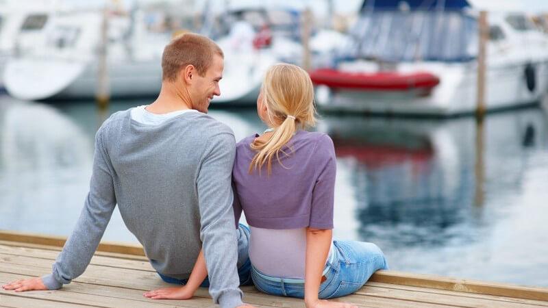 Junges Paar sitzt auf Steg am Hafen vor Booten