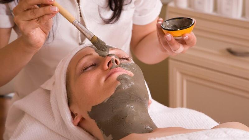 Kosmetikerin trägt einer jungen Frau eine braune Gesichtsmaske mit dem Pinsel auf