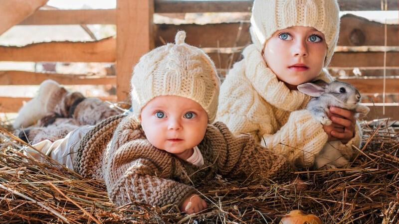 Kleines Mädchen mit Kaninchen auf dem Arm und ein Baby sitzen in einem Stall im Heu, warme Wollmützen an