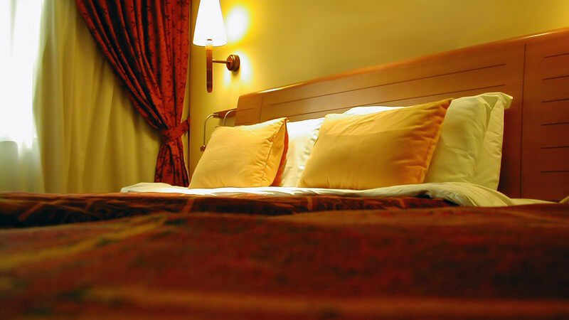 Hotelzimmerbett mit gelben Kissen und brennender Nachttischlampe an der Wand