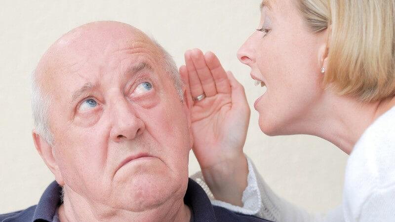 Ältere Frau sagt ihrem schwerhörigen Mann etwas ins Ohr