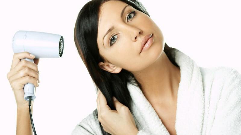 Schwarzhaarige Frau im weißen Bademantel föhnt ihr Haar