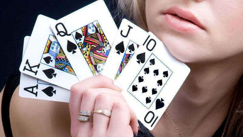 Junge Frau hält Spielkarten in die Kamera