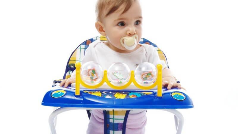 Baby in einem Laufstuhl auf weißem Hintergrund