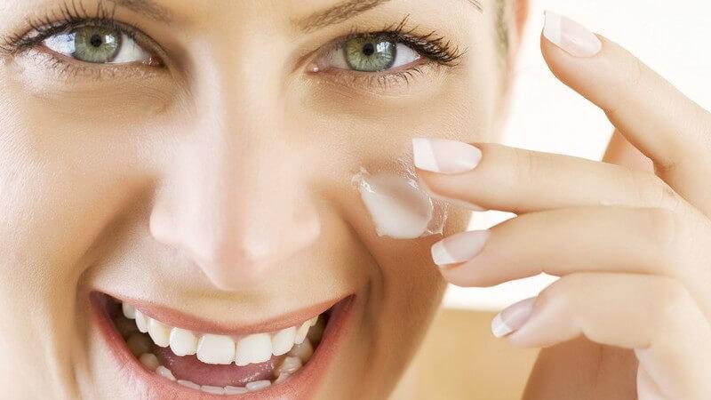 Lachende junge Frau cremt ihr Gesicht mit Creme ein