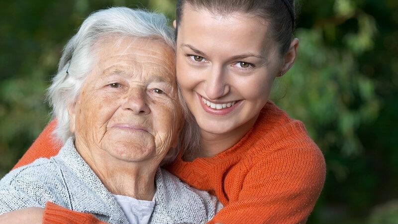 Alte Frau mit weißen Haaren wird von Tocher im Arm gehalten, beide lächeln in die Kamera