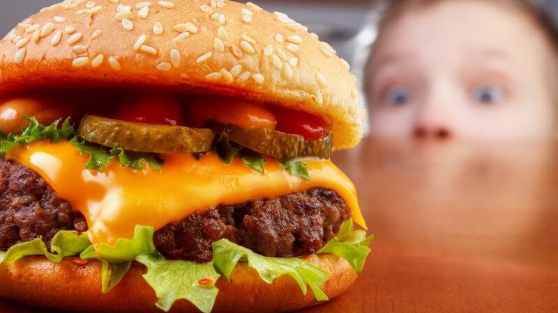 Dicker Burger auf einem Tisch, wird von einem Jungen im Hintergrund gierig beguckt