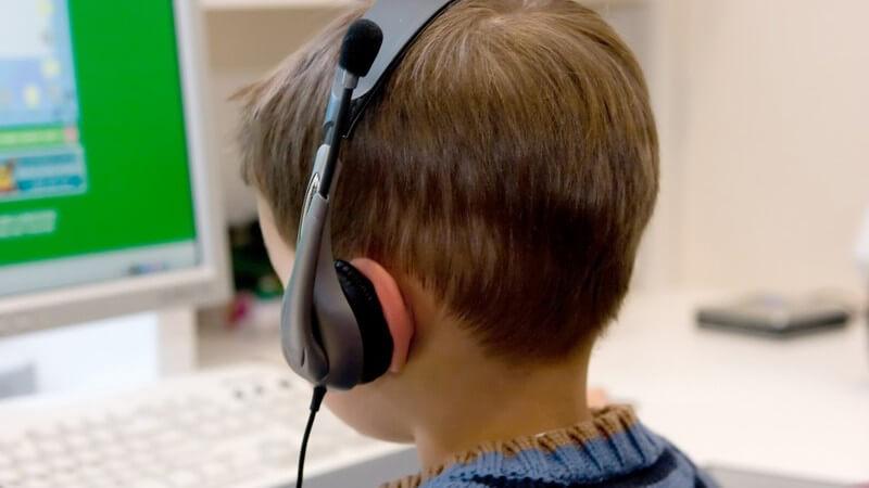 Kleiner Junge mit Headset sitzt vor dem Computer