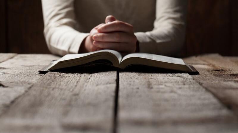 Zum Beten gefaltete Hände vor einer aufgeschlagenen Bibel auf altem Holztisch
