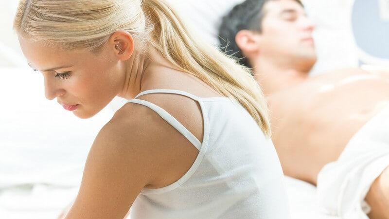 Junges Paar im Bett voneinander abgewandt