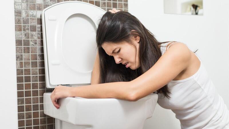 Frau mit Übelkeit lehnt über Toilettenschüssel, kurz vor dem Erbrechen