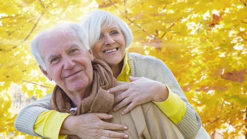 Äteres Paar im Herbst, Spaziergang, sie umarmt ihn von hinten