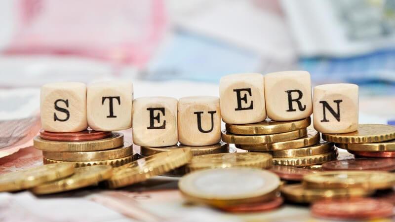 """Finanzen - Geldmünzen, darüber das Wort """"Steuern"""""""