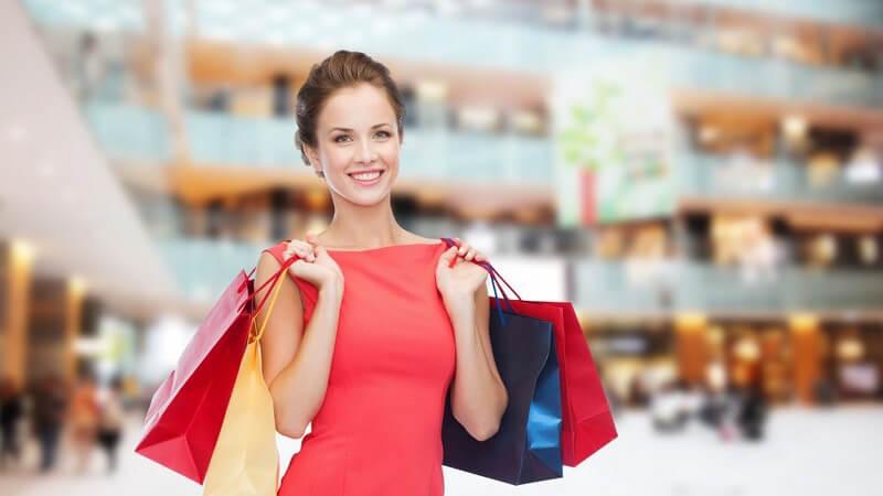 Frau beim Shopping mit Einkaufstüten in großem Einkaufszentrum