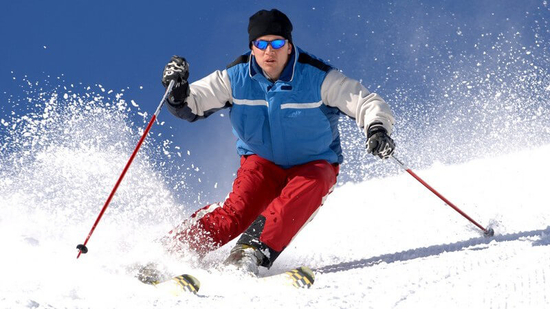 Skifahrer mit roter Hose und roten Stöcken bei einer schwungvollen Abfahrt