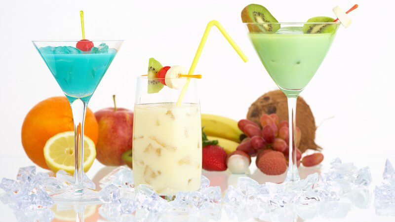 Verschiedene Cocktails in Gläsern zwischen Eiswürfeln, dahinter frisches Obst