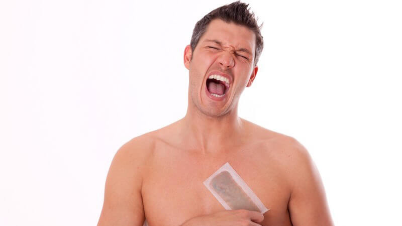 Mann mit nacktem Oberkörper schreit, Wachsstreifen auf Brust