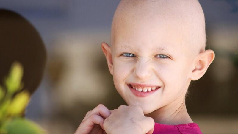 Krebskrankes Kind mit pinkem Oberteil und ausgefallenen Haaren (Glatze) blickt lächelnd in die Kamera