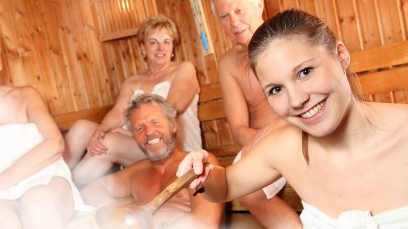Junge Frau macht einen Aufguss in der Sauna, hinter ihr sitzen mehrere Senioren