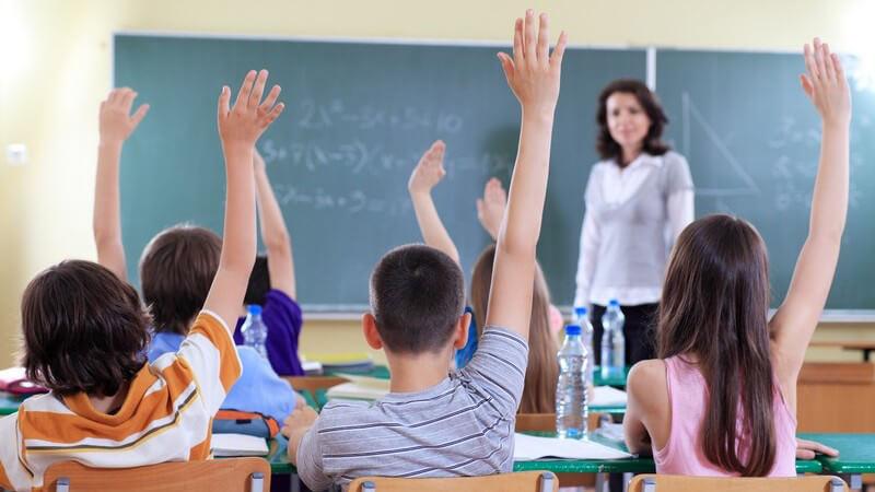 Rückansicht, Schüler in Klasse zeigen auf, vorne Lehrerin an Tafel