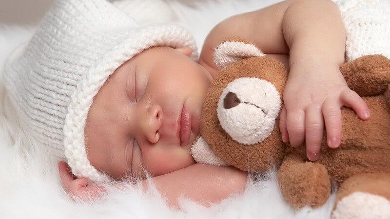 Schlafendes Baby mit Mütze, Neugeborenes mit Teddy im Arm auf Fell