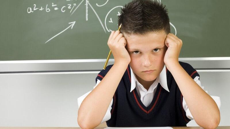 Junge vor Schultafel, stützt die Fäuse verärgert in die Schläfen
