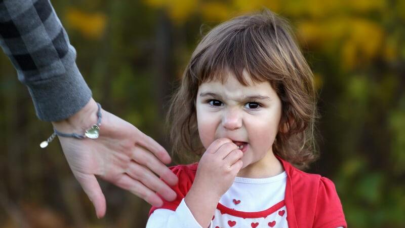 Mädchen in rot-weißem Oberteil hält trotzig die Hand an den Mund und verweigert einem Erwachsenen die Hand zu geben