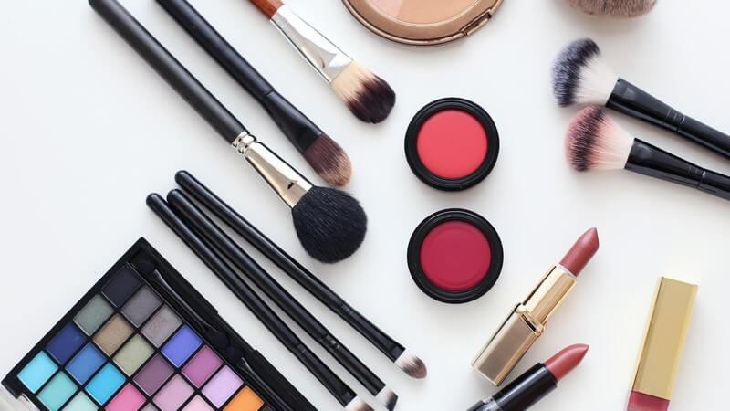 Sammlung diverser Kosmetika wie Make-up, Pinsel und Lippenstifte
