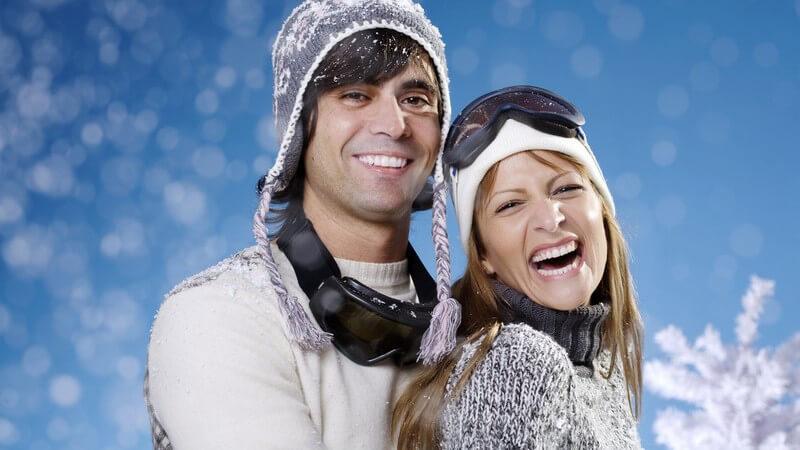 Junges lachendes Paar in Skiausrüstung, er steht hinter ihr, blauer Hintergrund mit Schneeflocken