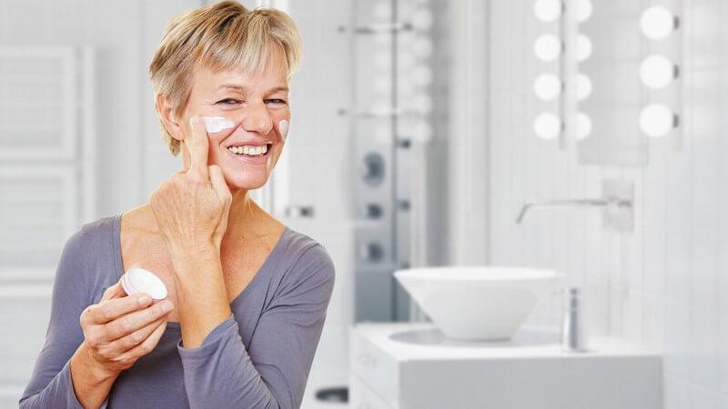 Seniorin mit Cremedose cremt sich im Badezimmer das Gesicht ein