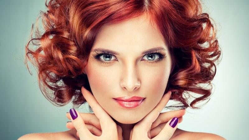 Model mit Make-up, lila Fingernägeln und roten Locken