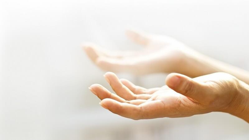 Zwei offene Hände mit der leeren Handinnenfläche nach oben, umgeben von leichtem Nebel und Licht