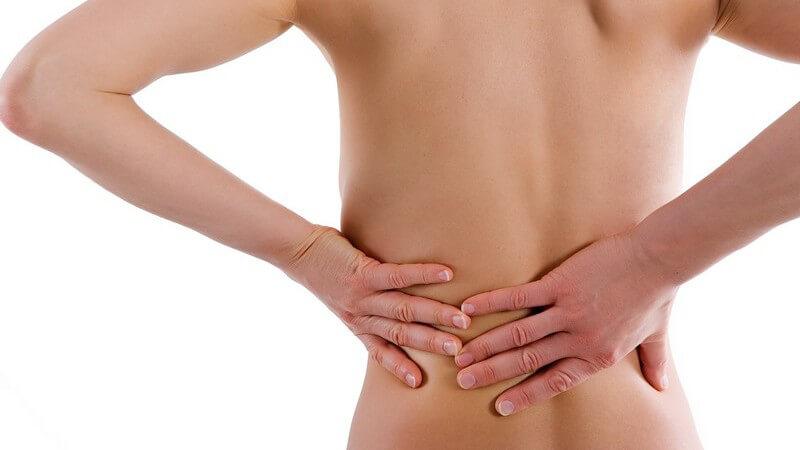 Symptome - Frau mit Rückenschmerzen fasst sich mit beiden Händen an den Rücken