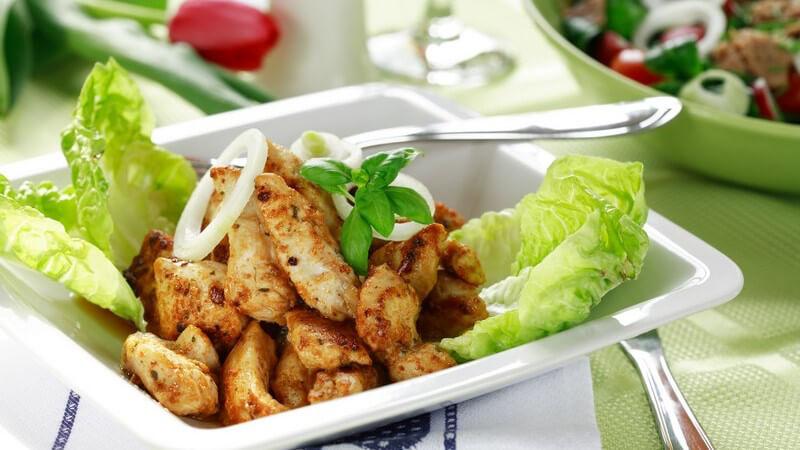 Gebratene Hähnchenstreifen mit Salat auf weißer, eckiger Schale