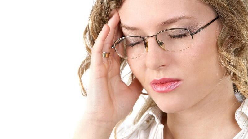 Kopfschmerzen - Blonde Frau mit Brille hat die Augen zu und fasst sich an die Schläfe