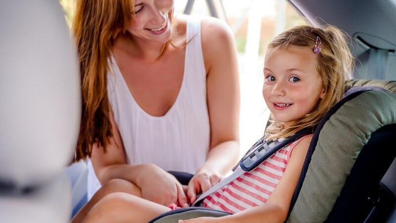 Mutter schnallt ihre Tochter im Kindersitz an