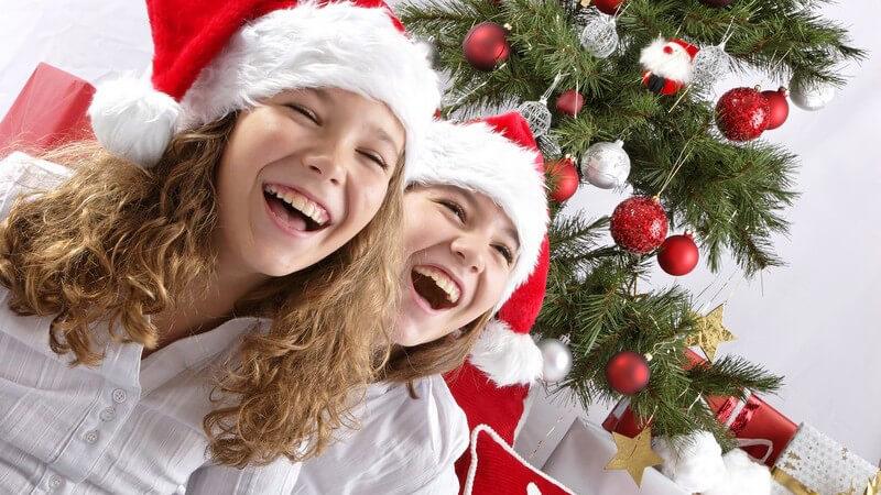Zwei Mädchen mit Nikolausmütze sitzen vor Weihnachtsbaum, lachen