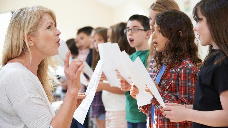 Kinder stehen nebeneinander, halten ein Notenblatt und singen im Chor, unterrichtet von einer blonden Lehrerin
