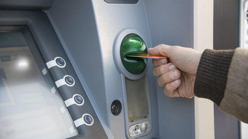 Bankkarte wird in den grünen Schlitz eines Geldautomaten gesteckt