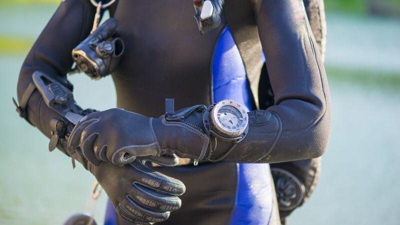Taucher in schwarz-blauem Neoprenanzug trägt Handschuhe und eine große Taucheruhr am linken Arm
