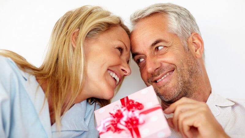 Paar lächelt sich an und reicht sich ein Geschenk