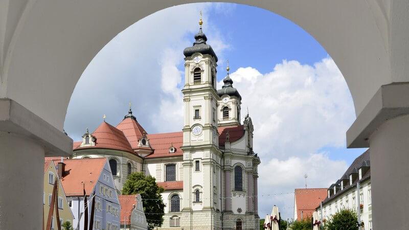 Blick durch einen weißen Torbogen auf das Kloster Ottobeuren in Bayern