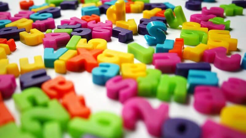 Bunte Buchstaben und Zahlen aus Kunststoff auf weißem Hintergrund