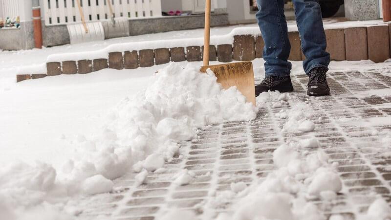 Mann mit Schneeschieber beim Schneeräumen vor dem Haus