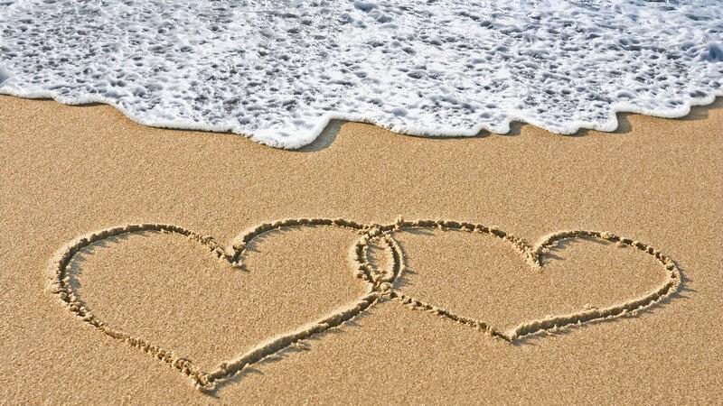 Zwei Herzen in Sand gemalt am Strand, dahinter kommt eine Welle