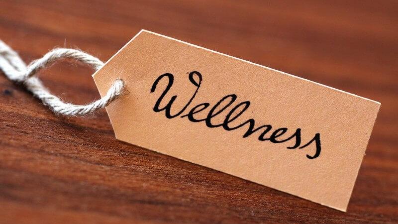 """Schild mit Aufschrift """"Wellness"""" an Schnur auf Holzuntergrund"""