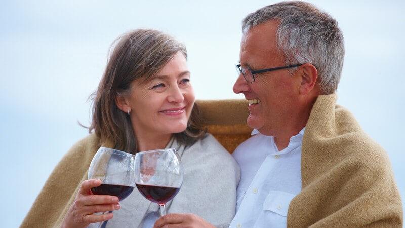 Älteres Paar sitzt in Decke gekuschelt und stößt mit Rotwein an
