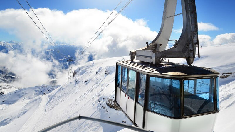 Schwarz-weiße Gondel schwebt über einem Skigebiet
