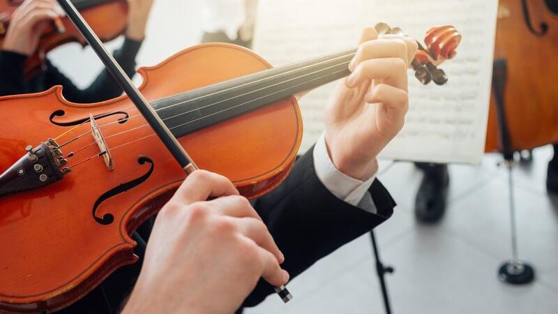 Geiger spielt in einem Orchester vor seinem Notenständer